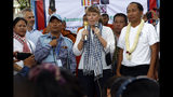 U.N. Special Rapporteur on Human Rights in Cambodia Rhona Smith, center, delivers a speech as Ath Thun, right, president of the Coalition of Cambodian Apparel Workers' Democratic Union, during a gathering marking the May Day at Tonle Sap river bank, in Phnom Penh, Cambodia, Wednesday, May 1, 2019. Some hundreds of workers staged a rally, demanding a better working condition. (AP Photo/Heng Sinith)