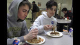 In this Friday, April 5, 2019 photo, Leo Dabelstein, left, and Kiran Bleakney eat lunch in the cafeteria at Burlington High School, in Burlington, Vt. The school's food service provider is preparing to comply with a Trump administration decision to roll back a rule that required only whole-grain rich foods for school meals. Burlington officials said they don't plan on abandoning whole-grain foods, but it gives them flexibility. (AP Photo/Wilson Ring)