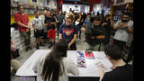 """A large group of fans gather to get autographs from Steve Aoki during a comic book signing of his new """"Neon Future"""" comic book series at Multiverse Corps. Comics on Thursday, May 2, 2019, in Miami. (AP Photo/Brynn Anderson)"""