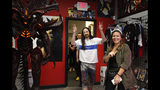 """Steve Aoki, center, gestures to his fans as he enters a comic book signing of his new """"Neon Future"""" comic book series at Multiverse Corps. Comics on Thursday, May 2, 2019, in Miami. Aoki imagines a future where humans live in harmony with technology. The story is set roughly 30 years from now in a United States that has outlawed advanced technology. A civil war is brewing between people who have integrated technology into their bodies and those who have not. (AP Photo/Brynn Anderson)"""