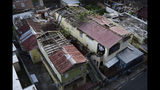 FILE - In this Nov. 15, 2017 file photo, buildings with their roofs damaged by the winds of Hurricane Maria are shown still exposed to weather conditions, in San Juan, Puerto Rico. Puerto Rico's government said Tuesday, April, 23, 2019, that it plans to demolish 16,000 structures that were heavily damaged by Hurricane Maria nearly two years ago. (AP Photo/Carlos Giusti, File)