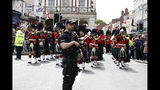 Armed police stand guard as the Royal Regiment of Scotland band march by, on the high street, in Windsor, south England, Tuesday, May 7, 2019, a day after Prince Harry announced that his wife Meghan, Duchess of Sussex, had given birth to a boy. The as-yet-unnamed baby arrived less than a year after Prince Harry wed Meghan Markle in a spectacular televised event on the grounds of Windsor Castle that was watched the world over. (AP Photo/Alastair Grant)