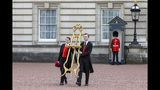 Palace officials carry the easel that will be placed in the forecourt of Buckingham Palace in London to formally announce the birth of a baby boy to Prince Harry and Meghan Duchess of Sussex Monday May 6, 2019. The official announcement is traditionally placed on public view in the courtyard of the palace. (AP Photo/Vudi Xhymshiti)