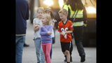 Students are led from a bus into a recreation center where they were reunited with their parents after a shooting at a suburban Denver middle school Tuesday, May 7, 2019, in Highlands Ranch, Colo. (AP Photo/David Zalubowski)