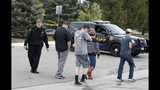 A Douglas County, Colo., Sheriff's Department deputy directs people back to their vehicles parked outside the STEM School Highlands Ranch after a shooting at the public charter school Tuesday, May 7, 2019, in Highlands Ranch, Colo. (AP Photo/David Zalubowski)