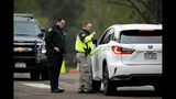 Douglas County Sheriff's Department deputies direct a motorist away from the scene outside STEM School Highlands Ranch a day after two students opened fire on students at the school, Wednesday, May 8, 2019, in Highlands Ranch, Colo. (AP Photo/David Zalubowski)