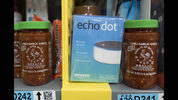 FILE - This Dec. 20, 2017, file photo shows the Amazon Echo Dot stocked on a shelf alongside jars of Garlic Chili Sauce at the Amazon Prime warehouse in New York. Consumer advocates say the kids' version of Amazon's Alexa won't forget what children tell it, even after parents try to delete the conversations. A coalition of groups on Thursday, May 9, 2019, is planning to ask the Federal Trade Commission to investigate whether Amazon is holding onto children's voice recordings and personal information longer than it should. (AP Photo/Mark Lennihan, File)