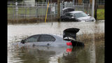 Two vehicles remain stuck in flooded Adams Street following an overnight storm Wednesday, May 8, 2019, in Porter, Texas. (Godofredo A. Vásquez/Houston Chronicle via AP)