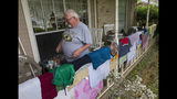 Ramond Giles walks past drying clothes, Wednesday, May 8, 2019, in Kingwood, Texas. Heavy rain battered parts of southeast Texas prompting flash flood warnings, power outages and calls for water rescues. (Jason Fochtman/Houston Chronicle via AP)