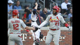 St. Louis Cardinals' Marcell Ozuna, right, is greeted by Paul DeJong hitting a three-run home, near Atlanta Braves catcher Brian McCann during the first inning of a baseball game Tuesday, May 14, 2019, in Atlanta. (Curtis Compton/Atlanta Journal-Constitution via AP)