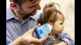 """In this undated photo provided by the University of Washington in May 2019, Dr. Randall Bly uses a uses a phone app and a paper funnel to focus the sound, to check his daughter for an ear infection, at the UW School of Medicine in Seattle. Bly and other researchers at the school have developed the system to """"hear"""" a warning sign of ear infections _ fluid build-up behind the eardrum. (Dennis Wise/University of Washington via AP)"""