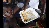 En esta imagen del 10 de mayo de 2019, un hombre da de comer a su hijo en un grandero utlizado como refugio en Peñitas, en la provincia de Darién, Panamá. (AP Foto/Arnulfo Franco)
