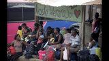 En esta imagen del 10 de mayo de 2019, un grupo de migrantes espera autobuses que los lleven al norte en Peñitas, en la provincia de Darién, Panamá. (AP Foto/Arnulfo Franco)