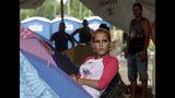 En esta imagen del 10 de mayo de 2019, la migrante cubana Lisandra Perez Molina descansa junto a su tienda en un refugio en Peñitas, en la provincia de Darién, Panamá. Pérez dio a luz el 14 de abril en un poblado indígena antes de llegar a Peñitas, pero estaba cansada de esperar en el abarrotado refugio. (AP Foto/Arnulfo Franco)