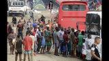 En esta imagen del 10 de mayo de 2019, un grupo de migrantes esperan para subir a un autobús que los lleve en su viaje al norte, en Peñitas, en la provincia de Darién, Panamá. (AP Foto/Arnulfo Franco)