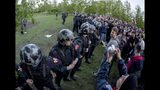 Police officers block demonstrators protesting plans to construct a cathedral in a park in Yekaterinburg, Russia, Tuesday, May 14, 2019. A group that monitors police actions and political repression in Russia says at least 12 people have been detained in Russia's fourth-largest city while protesting plans to start construction of a cathedral in a city park. (AP Photo/Anton Basanayev)
