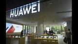 Compradores chequean smartphones en una tienda de Huawei en Hangzhou, en la provincia de Zhejiang, en el este de China, el 16 de mayo de 2019. (Chinatopix via AP)