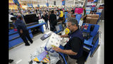 FILE - In this Nov. 9, 2018, file photo Walmart associate Javaid Vohar, right, checks out customers at a Walmart Supercenter in Houston. Walmart Inc. reports earnings on Thursday, May 16, 2019. (AP Photo/David J. Phillip, File)