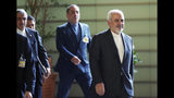"""Iranian Foreign Minister Mohammad Javad Zarif, right, walks to meet Japanese Prime Minister Shinzo Abe at Abe's official residence in Tokyo Thursday, May 16, 2019. Iran's foreign minister has said his country is committed to an international nuclear deal and criticized escalating U.S. sanctions """"unacceptable"""" as he met with Japanese officials in Tokyo amid rising tensions in the Middle East.(AP Photo/Eugene Hoshiko, Pool)"""