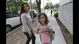 """In this Monday May 13, 2019 photo Christina Richner, walks down the street with her children Julian, far right, and Olivia at Horace Mann School in Beverly Hills, Calif. Richner, said of her children that they have gone through so many emergency drills that """"their reflexes will kick in"""" during a shooting. The students are trained to gather in a corner with the classroom's lights out and blinds drawn in a lockdown situation, according to social studies teacher Laura Stark. (AP Photo/Richard Vogel)"""