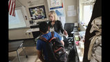 In this Monday May 13, 2019 photo social studies teacher Laura Stark gives a hand to a student after class at Horace Mann School in Beverly Hills, Calif. The students are trained to gather in a corner with the classroom's lights out and blinds drawn in a lockdown, Stark said. Staffers check in via the Share911 app to share information, including if any kids are missing or injured. (AP Photo/Richard Vogel)
