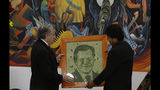 Secretary General of the Organization of American States Luis Almagro, left, receives a portrait of himself designed with painted coca leaves, from Bolivia's President Evo Morales, at the government palace in La Paz, Bolivia, Friday, May 17, 2019. Almagro is in Bolivia on an official visit. (AP Photo/Juan Karita)