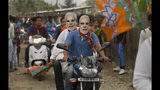 FILE - In this April 2, 2019 file photo, Bharatiya Janata Party (BJP) supporters wear masks of Indian Prime Minister Narendra Modi and ride a motorbike during an election campaign rally ahead of general elections in Borhola village, Assam state, India. The final phase of India's marathon general election will be held on Sunday, May 19. The first of the election's seven staggered phases was held on April 11. Vote counting is scheduled to start on May 23. India has 900 million eligible voters. (AP Photo/Anupam Nath, File)