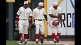 Cincinnati Reds right fielder Yasiel Puig, right, holds his arm alongside center fielder Nick Senzel, center, and left fielder Jose Peraza, left, after colliding with the outfield wall on a play in the sixth inning of a baseball game against the Los Angeles Dodgers, Sunday, May 19, 2019, in Cincinnati. (AP Photo/John Minchillo)