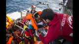 FILE - In this Friday, Dec. 21, 2018 file photo, a baby is loaded into the rescue vessel of the Spanish NGO Proactiva Open Arms, after being rescued in the Central Mediterranean Sea at 45 miles (72 kilometers) from Al Khums, Libya. A judge in Sicily has dropped an investigation against two member of the Spanish aid group Proactiva Open Arms deriving from a tense high-seas standoff last year when the crew refused to hand over 218 migrants rescued at sea to the Libyan coast guard. Proactiva welcomed the decision to drop the investigation into criminal association and aiding illegal migration Wednesday, calling it ''an additional step toward the truth.'' The group stated that it has always operated according to international roles. (AP Photo/Olmo Calvo, File)