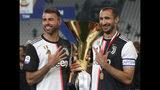 Andrea Barzagli (izquierda) y Giorgio Chiellini de la Juventus posan tras obtener el trofeo de la Serie A italiana, en Turín, Italia, el domingo 19 de mayo de 2019. (AP Foto/Antonio Calanni)