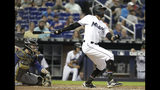 Miami Marlins' Rosell Herrera watches after hitting a double in the sixth inning during a baseball game against the New York Mets, Sunday, May 19, 2019, in Miami. At left is New York Mets catcher Tomas Nido. (AP Photo/Lynne Sladky)