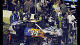 A NASCAR official tries to get between drivers Ryan Newman, in green suit near the car's hood, and Clint Bowyer after the NASCAR All-Star Race at Charlotte Motor Speedway in Concord, N.C., Saturday, May 18, 2019. (AP Photo/Mike McCarn)