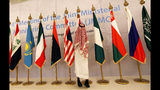 A Saudi worker adjusts flags of participating countries before a meeting of energy ministers from OPEC and its allies to discuss prices and production cuts, in Jiddah, Saudi Arabia, Sunday, May 19, 2019. The meeting takes places as tensions flare in the Persian Gulf after the U.S. ordered bombers and an aircraft carrier to the region over an unexplained threat they perceive from Iran, which comes a year after the U.S. unilaterally pulled out of Tehran's nuclear deal with world powers and reimposed sanctions on Iranian oil.(AP Photo/Amr Nabil)