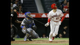 Los Angeles Angels' Shohei Ohtani, right, flies out to center field, while Kansas City Royals catcher Martin Maldonado, center, and home plate umpire Chris Guccione watch during the third inning of a baseball game in Anaheim, Calif., Saturday, May 18, 2019. (AP Photo/Alex Gallardo)