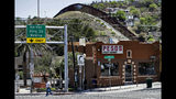"""FILE - In this April 10, 2018, file photo, the International border cuts through Nogales, Sonora, Mexico, rear, as seen from Nogales, Ariz. Federal court records say a Border Patrol agent in Arizona sent texts referring to migrants as """"savages"""" and """"subhuman"""" the month before allegedly knocking over a Guatemalan man with his patrol vehicle. The filings in U.S. District Court in Tucson earlier in May 2019 say Agent Matthew Bowen sent the text messages in November 2017, weeks before allegedly knocking down the migrant. He goes on trial Aug. 13. He has pleaded not guilty to depriving the migrant of his rights and falsifying records. (AP Photo/Matt York, File)"""