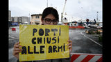 """An activist holds up a sign with writing reading in Italian """"Ports closed to weapons"""" as she demonstrates after Saudi Arabian freighter Bahri Yambu docked in Genoa's port, Italy, Monday, May 20, 2019. The freighter allegedly carrying weapons that could be used in the war in Yemen is scheduled to load further cargo before departing for the Saudi port of Jeddah late Monday despite protests by harbor workers, according to the Italian news agencies. (Luca Zennaro/ANSA via AP)"""