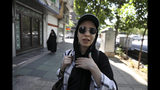 """In this Friday, May 17, 2019 photo, civil servant Masumeh Izadpanah speaks during an interview in downtown Tehran, Iran. """"When someone keeps trying to scare you it means that they think they are not yet ready for war. When someone really wants war it starts the war right away. Like when Iraq attacked us, all of a sudden bombs were dropped,"""" she told the AP. """"But right now America just says, 'I'm coming,' to scare Iran."""" (AP Photo/Vahid Salemi)"""