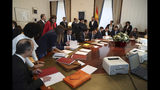 The leader of the Catalonian ERC party Oriol Junqueras, 3rd right, councilor Josep Rull, 5th right, and Jordi Sanchez, president of the Catalan National Assembly, 4th left, sign documents inside the Spanish parliament in Madrid, Spain, Monday May 20, 2019. The five separatist leaders on trial for Catalonia's 2017 secession attempt who were elected to the Spanish Parliament in April 28 elections have been escorted by police to pick up their official parliament credentials. The Supreme Court is allowing the five politicians to get their credentials on Monday and attend the opening session of the new Parliament on Tuesday. (J.J. Guillen/Pool Photo via AP)