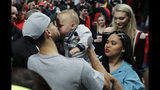 Golden State Warriors guard Stephen Curry, left, kisses his son Canon, as his wife Ayesha, lower right, looks on, at the end of Game 4 of the NBA basketball playoffs Western Conference finals against the Portland Trail Blazers, Monday, May 20, 2019, in Portland, Ore. The Warriors won 119-117 in overtime. (AP Photo/Ted S. Warren)