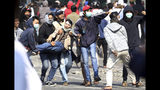 Supporters of Indonesian presidential candidate Prabowo Subianto carry an injured man during a clash with Indonesian police in Jakarta, Indonesia, Wednesday, May 22, 2019. Supporters of the unsuccessful presidential candidate clashed with security forces and set fire to a police dormitory and vehicles in the Indonesian capital on Wednesday after the release of official election results. (AP Photo/Achmad Ibrahim)