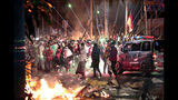 Fire crackers explode near supporters of presidential candidate Prabowo Subianto during clashes with the police in Jakarta, Indonesia, Wednesday, May 22, 2019. Indonesian President Joko Widodo said authorities have the volatile situation in the country's capital under control after six people died Wednesday in riots by supporters of his losing rival in last month's presidential election. (AP Photo/Dita Alangkara)