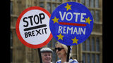 Anti Brexit campaigners hold banners near Parliament in London, Wednesday, May 22, 2019. British Prime Minister Theresa May was under pressure Wednesday to scrap a planned vote on her tattered Brexit blueprint - and to call an end to her embattled premiership - after her attempt at compromise got the thumbs-down from both her own Conservative Party and opposition lawmakers. (AP Photo/Kirsty Wigglesworth)