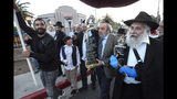 Howard Kaye, center, husband of Lori Kaye, carries the new Torah as Rabbi Yisroel Goldstein, right, and other members of the Chabad of Poway synagogue celebrate the completion of the new scroll dedicated to Lori Kaye, who was killed when a gunman attacked the synagogue in April on Wednesday, May 22, 2019, in Poway, Calif. (Hayne Palmour IV/The San Diego Union-Tribune via AP)