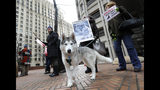 FILE - In this Thursday, March 7, 2019 file photo, Ella, a Siberian Husky, stands with her owner, Tracey Conway, second from right, during a protest at the Henry M. Jackson Federal Building in Seattle. Protesters were opposing a proposal made Wednesday by the Trump administration to lift protections for gray wolves across the Lower 48 states. The plan has gotten a mixed reaction in Washington state. (AP Photo/Ted S. Warren)