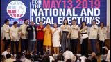 Doce senadores recién nombrados hacen gestos asociados con sus partidos políticos en la Comisión Electoral en el suburbio de Pasay, al sur de Manila, Filipinas, el 22 de mayo de 2019. (AP Foto/Bullit Marquez)