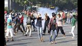 Supporters of Indonesian presidential candidate Prabowo Subianto run from smoke of tear gas fired by police officers in Jakarta, Indonesia, Wednesday, May 22, 2019. Supporters of the unsuccessful presidential candidate clashed with security forces and set fire to a police dormitory and vehicles in the Indonesian capital on Wednesday after the release of official election results. (AP Photo/Achmad Ibrahim)