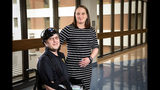 In this image provided by University of Utah Health, Montana Highway Patrol Trooper Wade Palmer and his wife, Lindsey, pose at University of Utah Health, Wednesday, May 22, 2019, in Salt Lake City. Palmer returned home to Montana on Wednesday to continue his recovery, just over two months after he was shot in the head, face and neck while investigating a fatal shooting. Doctors said Wade Palmer suffered a traumatic brain injury and is unable to speak but seems to understand what is being said. (University of Utah Health via AP)