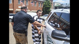 Oxford, Miss. police officer Matt Kinne, right, who has been charged with murder in the death of Dominique Clayton, is placed in the back of a patrol car by Major Alan Wilburn of the Lafayette County Sheriff Department following a hearing at the Lafayette County Courthouse in Oxford, Miss. on Wednesday, May 22, 2019. (Bruce Newman/The Oxford Eagle via AP)