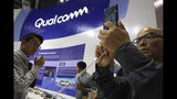 FILE - In this Nov. 6, 2018 file photo, attendees look at the latest technology from Qualcomm at the China International Import Expo in Shanghai. Qualcomm's stock is tumbling before Wednesday's market open on May 22, 2019, after a federal judge ruled that the company unlawfully stifled cellphone chip market competition and charged excessive licensing fees. (AP Photo/Ng Han Guan, File)