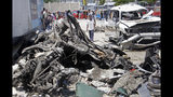 Somalis walk near the wreckage after a suicide car bomb attack in the capital Mogadishu, Somalia Wednesday, May 22, 2019. A police spokesman said the attack killed at least six people and injured more than a dozen, while Islamic extremist group al-Shabab claimed responsibility for the blast, saying it targeted vehicles carrying government officials. (AP Photo/Farah Abdi Warsameh)